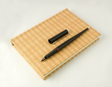 Black pen and notebook on white background Stock Photo - 19685965