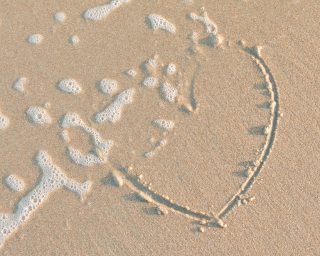 Melting heart on sand