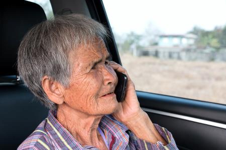Senior woman using mobile phone in car