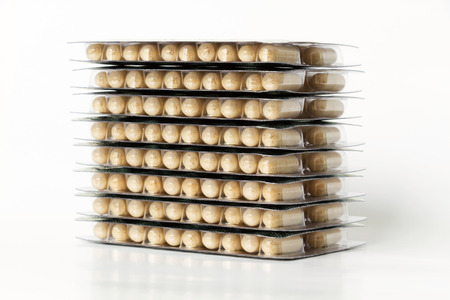 Stacked of herb capsule on white background  Stock Photo