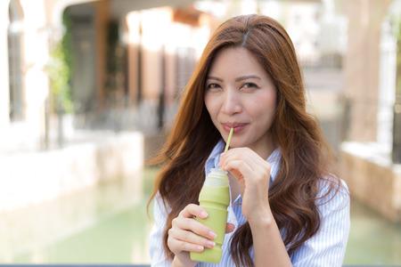 Beautiful Asian woman drink ice green tea