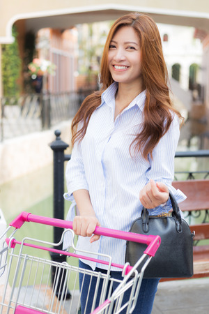 woman shopping cart: Woman with smiling face and shopping cart