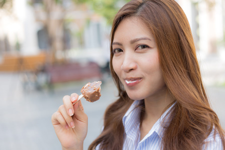 Asian woman eating ice cream with blur background Stock Photo