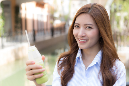 Happy young woman with ice green tea in her hand, blurred background