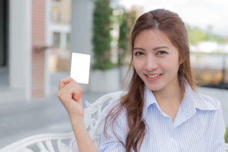 Asian woman with smiling face and white blank card in her hand