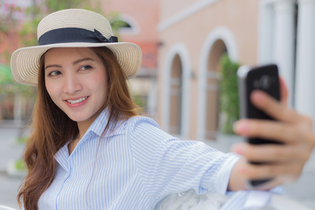 Asian woman taking selfie, blurred background