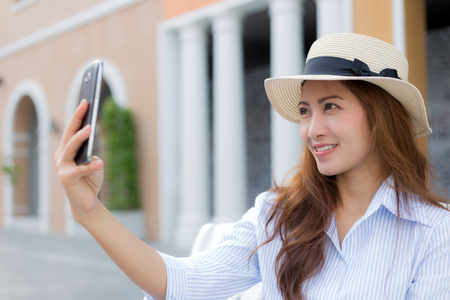 Beautiful Asian woman taking selfie, blurred background Stock Photo