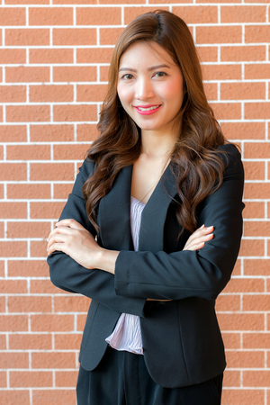 Asian business woman with crossed arms standing against brick wall