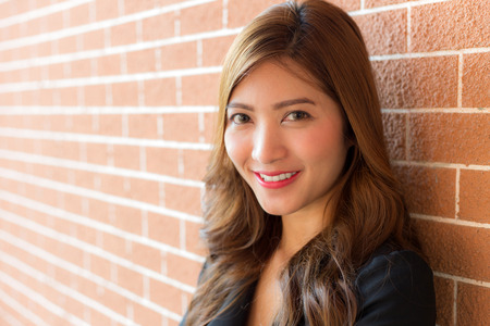 Asian business woman with smiling face against brick wall Stock Photo