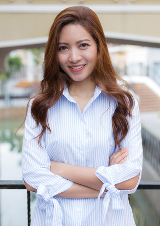 Portrait of Asian woman standing crossed arms with smiling face and blurred background