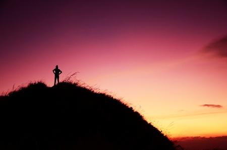 Žena stojí na vrcholu hory v soumraku scéně Thajsku