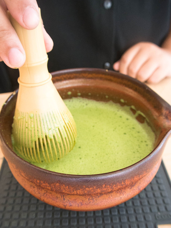 ceremic: Mixing Japanese Matcha Green Tea in a Ceremonial Bowl with Whisk Stock Photo