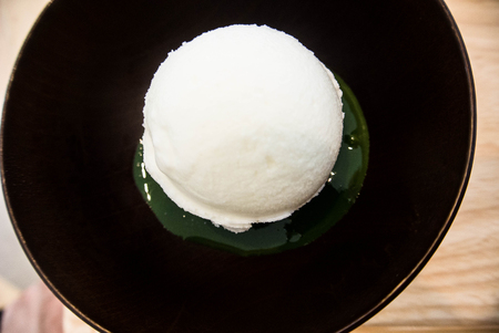 vanilla ice cream scoop top on creamy Green tea matcha in bowl on a wooden background Stock Photo