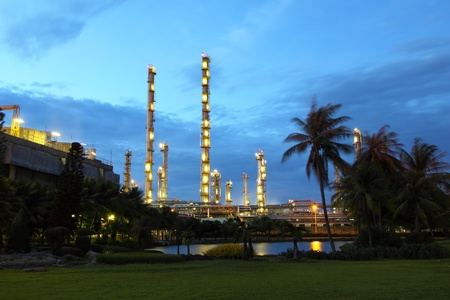 Petrochemical plant behind a garden at dusk
