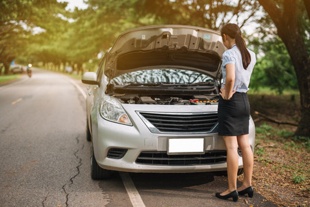 attractive brunette in front of her car broken down car. Archivio Fotografico