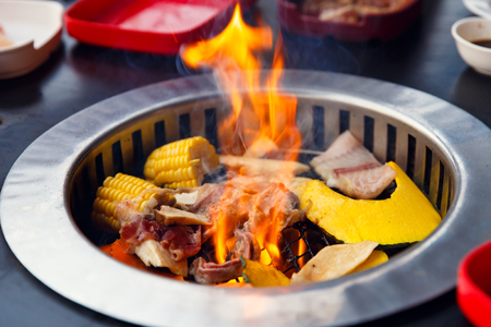 white backing: Yakiniku grill on a barbecue on the grill with fish meat and vegetables.top view Stock Photo