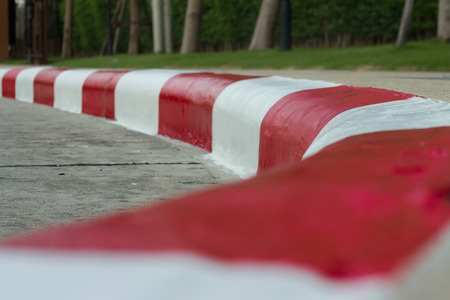 breaking the rules: red -white traffic lines on footpath Stock Photo