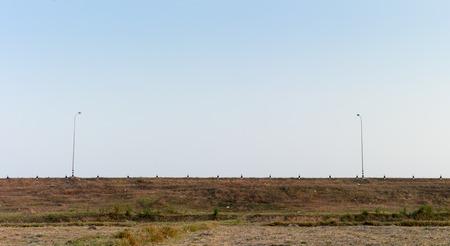 empedrado: La carretera asfaltada en un paisaje rural, kil�metro y un poste de energ�a Foto de archivo