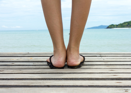 long toes: Female feet and slippers with background sea