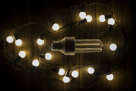 uniqueness: glowing bulb uniqueness concept on brown wooden table