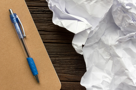 writer's block: Working with crumpled paper, pen and book on wooden table background
