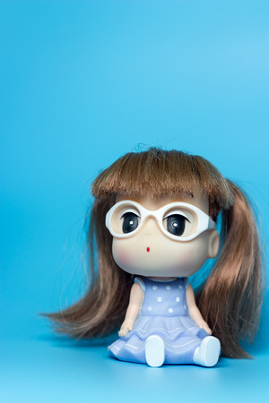 sit down: girl doll sit down on blue background