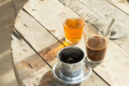 condensed: Coffee brewed in traditional vietnamese style with Tea on wooden table Stock Photo