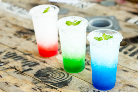 italian soda with mint leaves on ice, colorful of fruit juice on wooden table