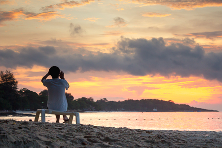 somebody sit on bench at the beach and take photo look to sunrise, Koh Samet Thailand