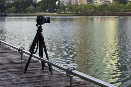 camera on tripod take picture at park with lake Stock Photo