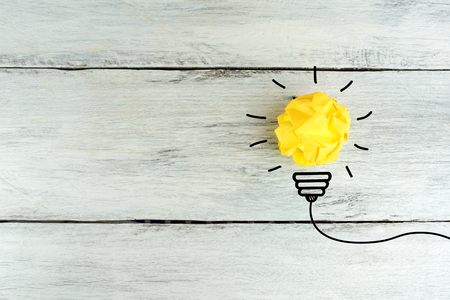 great idea concept with crumpled office paper and light bulb on white wooden table