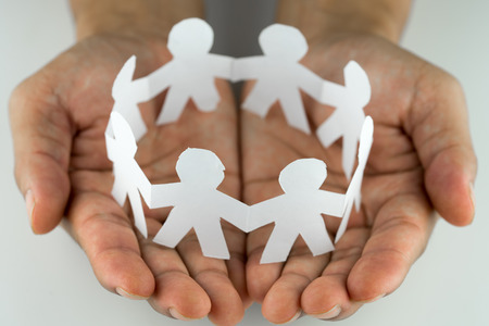 Paper people in the hands. Concept of insurance, social protection and support. Stockfoto