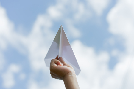 plane paper in children hand and blue sky in cloudy day. business concept. Stock Photo