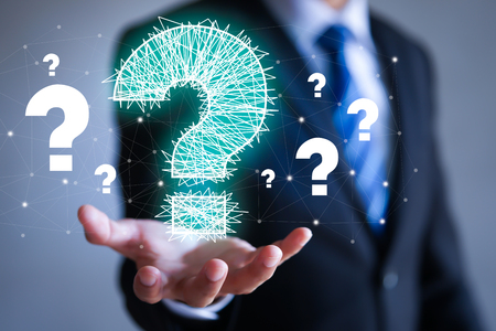 Businessman on blurred background holding hand drawn question marks in his hand