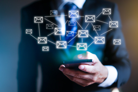 Business man using modern mobile phone with email icons around it.
