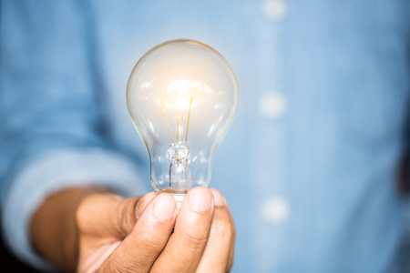 hand businesswoman holding light bulb, innovation and inspiration concept