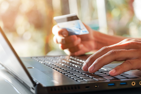 Hands using computer and holding credit card