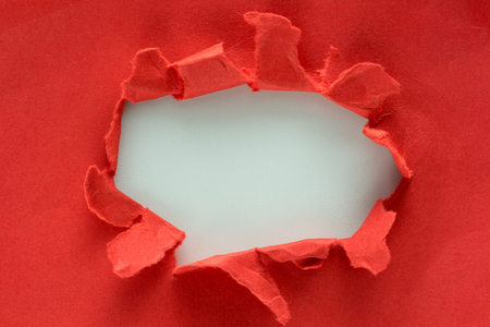 Hole in the red paper with torn sides Foto de archivo