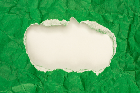 Hole in the green paper with torn sides