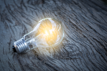 glowing bulb on the brown wooden background