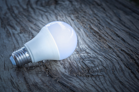 White light bulb glowing on the wood ground
