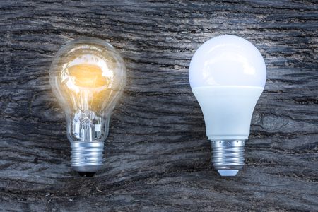 LED and Fluorescent bulb with light on on wooden background, Power energy saving concept. Stockfoto