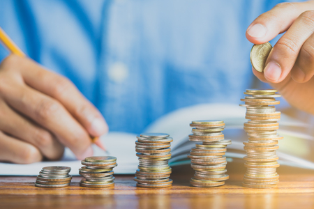 hand add coin to coin stack, saving money concept and finance accounting concept.