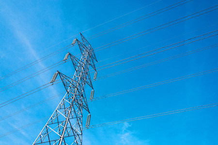 High voltage pole with blue sky background, Electric transmission line system for large industrial plants.