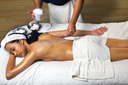 african american spa: Sea Salt Scrub Massage Treatment in a spa setting.