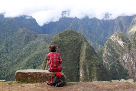 girl sitting on the edge of rock in Machu Picchu, Peru photo
