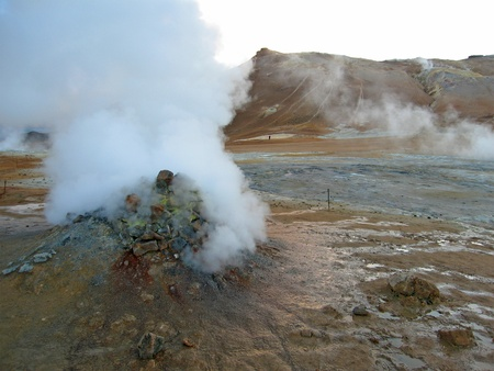 erupting geyser of steam with sulfur deposits, Iceland photo