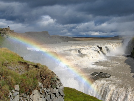 tourist spots: Waterfall Gullfoss with big rainbow and dark blue clouds, Iceland Stock Photo