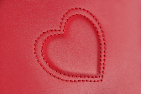 Convex embroidery in shape of two hearts nested in each other, on pink leather, side view, closeup