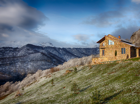 lonely stone house on the hill on the background of snowy mountains, hdr, Armenia Stock Photo